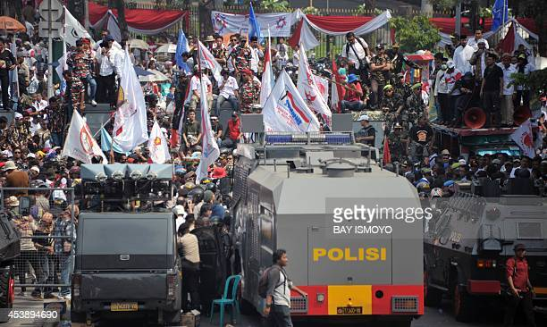 Indonesian antiriot police stand guard next to presidential candidate Prabowo's supporters near the constitutional court in Jakarta on August 21...