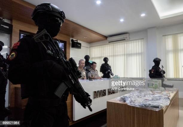 Indonesian antiterror police personnel keep watch during a press conference and media presentation of seized material and evidence from recent...