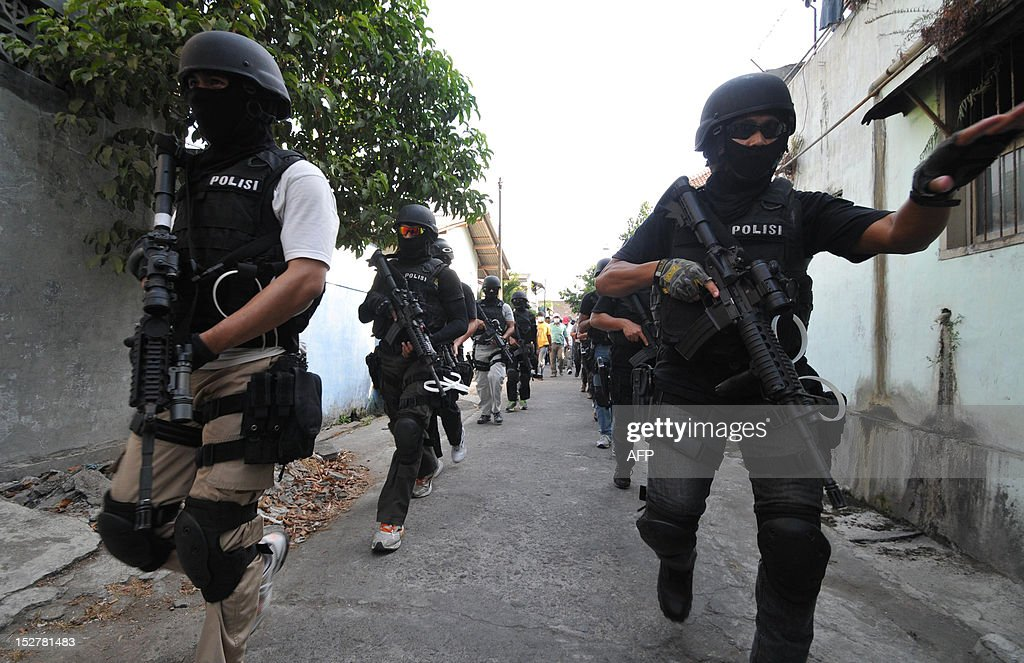 Indonesian antiterror policemen from Detachment 88 investigate a house belonging to a terror suspect in Solo on September 26 following a raid on...