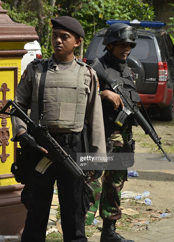 Indonesian armed police and soldiers stand on alert at Ungaran village in Kebumen, Central Java, on May 9, 2013, as they raided a house where suspected terrorists were hiding. Indonesian police have shot dead seven terror suspects in raids over the past two days, including several with alleged links to a plot to bomb the Myanmar embassy, officials said. Thirteen suspects were captured alive as an elite police unit swooped on houses across the country's main island of Java, in the biggest counter-terrorism operation in Indonesia for months. AFP PHOTO / Zain FIRMANSYAH