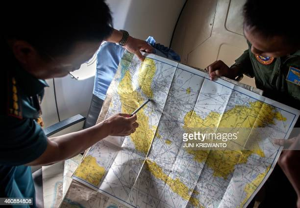 Indonesian Army personnel read a map during a search and rescue operation for missing Malaysian air carrier AirAsia flight QZ8501 over the waters of...