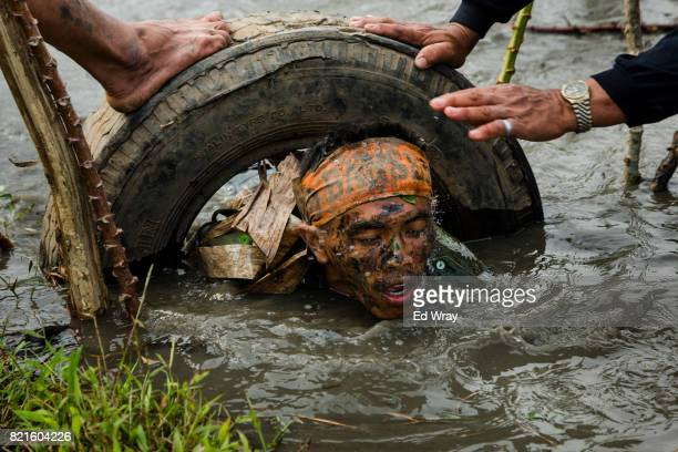 Indonesian Banser recruits crawl through the mud of an irrigation canal as part of a three day induction course on July 23 2017 in Kebumen Indonesia...