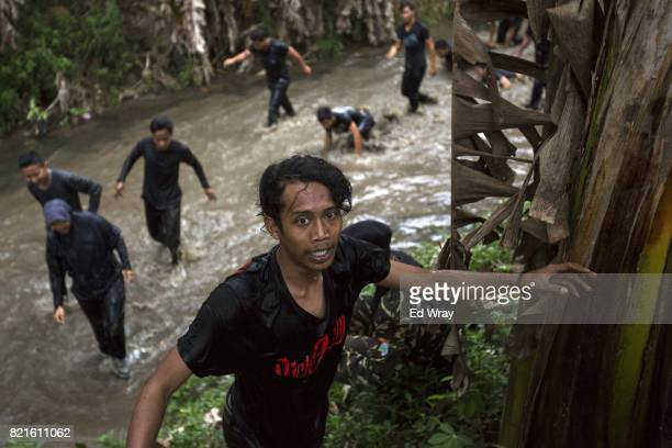 Indonesian Banser recruits emerge from a river after crawling through the mud as part of a three day induction course on July 21 2017 in Kebumen...