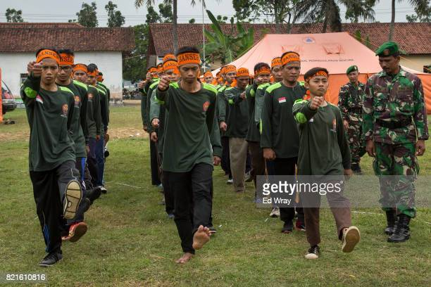 Indonesian Banser recruits practice marching under the eyes of an Indonesian soldier brought in to teach parade drills during a three day induction...