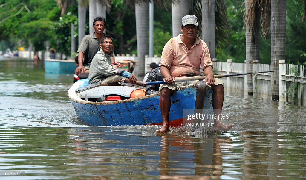 Indonesian boat men transport passengers down a street inundated by floodwaters at a luxury housing complex in Jakarta on January 20, 2013. The death toll from floods in Indonesia's capital Jakarta rose to 15 on January 19 after rescuers found another four bodies. The floods are the worst to hit the capital since 2007 and forced 18,000 people from their homes.