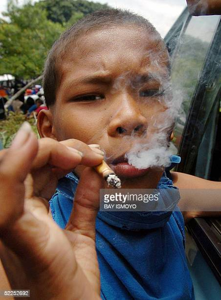 Indonesian boy smokes a cigarette in a public area in Jakarta 28 February 2005 Smoking kills about 57000 Indonesians each year through fatal heart...