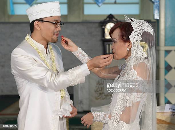 Indonesian bride Sitta Kusuma and groom Adam Afiezan feed each other as they take part in their Muslim wedding ceremony at a mosque in Jakarta on...