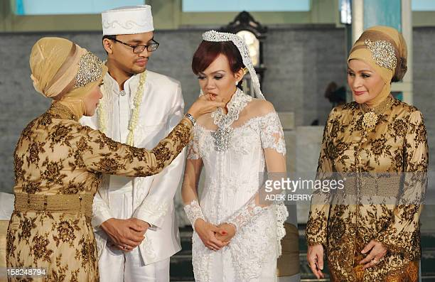 Indonesian bride Sitta Kusuma is feed by her mother Sri Budi Utami as the groom Adam Afiezan and his mother Feraluna Nasution look on during their...
