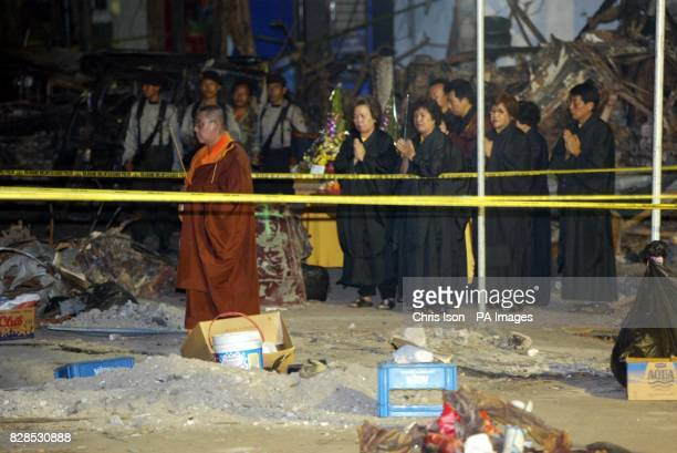 Indonesian buddhist monks pray at the bomb site as an eerie silence falls over the normally bustling Legian Street in Kuta Bali at 1130pm today...