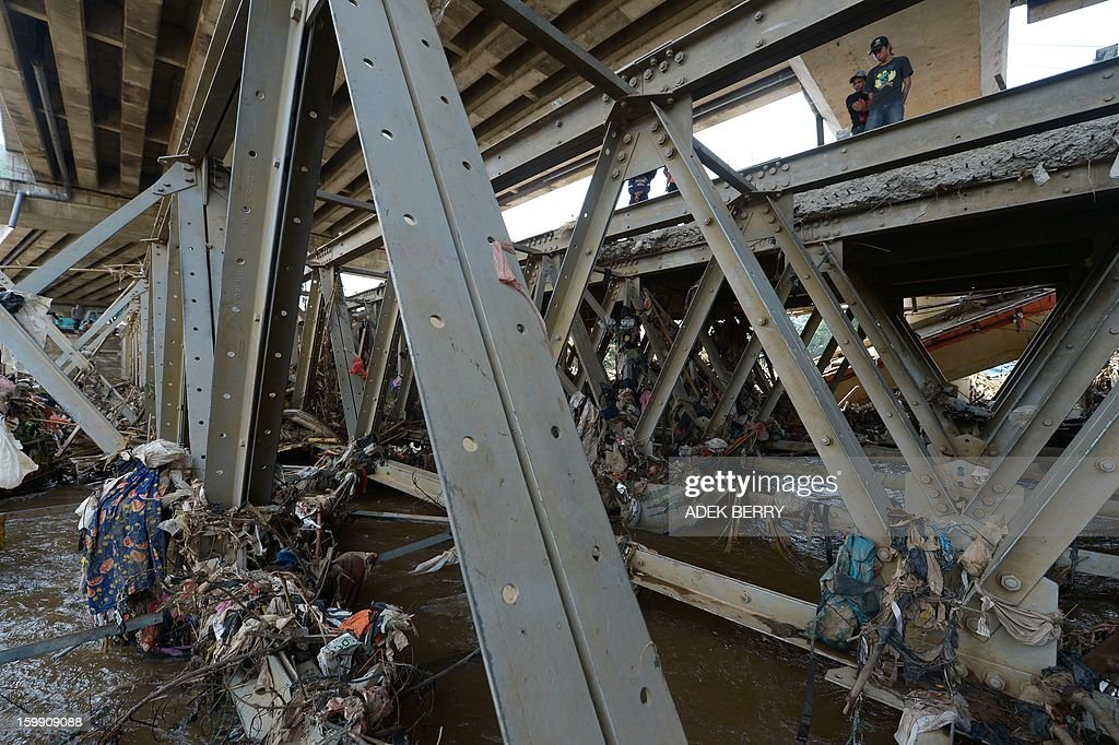 Indonesian bystanders look at the polluted Ciliwung river full of garbages following heavy floods in Jakarta on January 23, 2013. A spokesman for Indonesian National Disaster Mitigation Agency (BNPB) said more than 30,000 people were still living as refugees on January 22, while 20 people were killed during the widespread flooding that hit Jakarta last week.