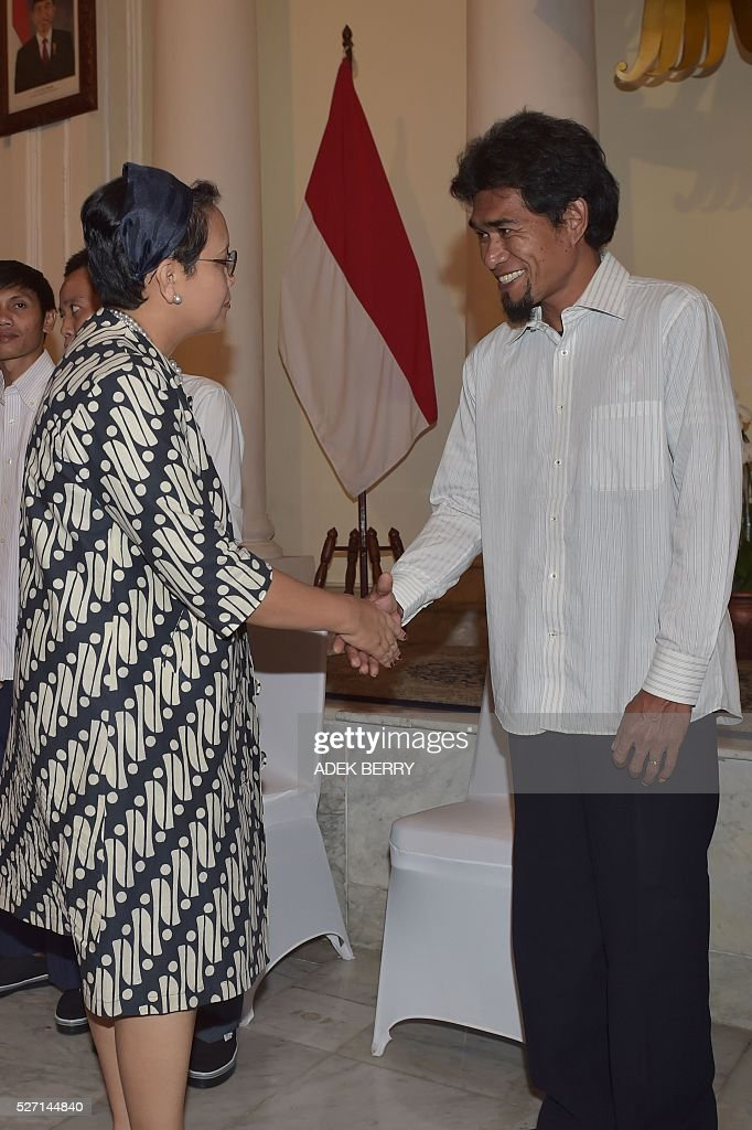 Indonesian captain of the Brahma12 tugboat Peter Tonsen Barahama (R) shakes hands with Indonesian Foreign Minister Retno Marsudi (L) during ceremony to mark a hostages being handed over to families at the Foreign Ministry office in Jakarta on May 2, 2016, after ten Indonesian sailors held hostage by Abu Sayyaf Islamic militants returned home on May 1 after being freed in the southern Philippines, less than a week after the gunmen beheaded a Canadian captive. About five weeks after being abducted, the 10 tugboat crew turned up outside the house of the provincial governor on the remote Philippine island of Jolo. They flew back to Jakarta later the same day, arriving on a private plane at an air force base before being driven away in a minibus without speaking to reporters. / AFP / ADEK
