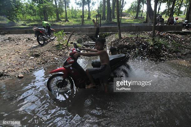 Indonesian child wash motorcycle at Coyo water source in Purwodadi Central Java of Indonesia on May 21 2014 Access to clean safe water is an...