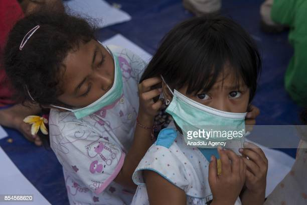 Indonesian children evacuated from their home due to the volcanic activities of Mount Agung practise to wear masks in a temporary shelter in...