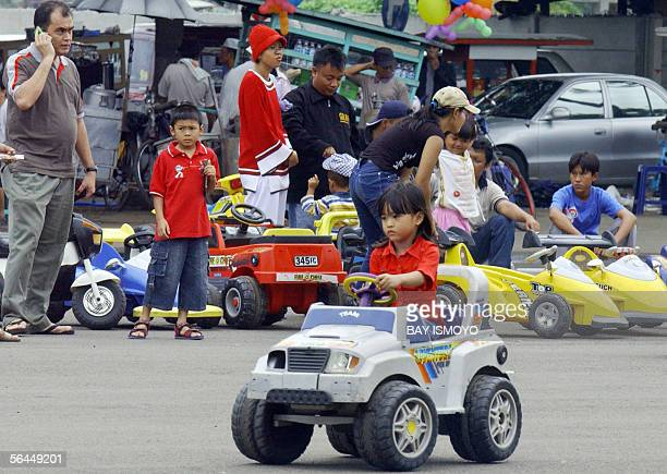 Indonesian children from middlelow class family drive 30 cent rent electric car at a public park in Jakarta 18 December 2005 Children experience...