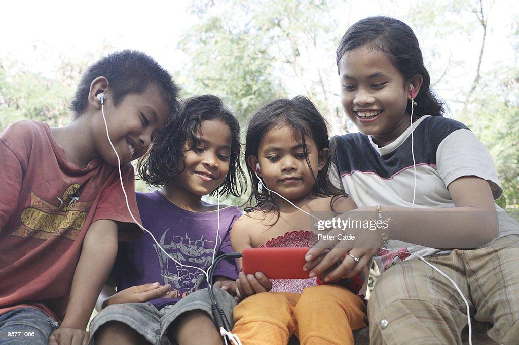 indonesian children listening to mp3 player : Stock Photo