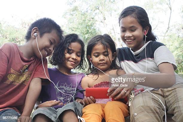 indonesian children listening to mp3 player