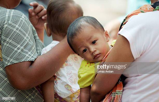 Indonesian children queue with their mothers at an immunisation post to receive polio vaccination drops August 30 2005 in Jakarta Indonesia Amid...