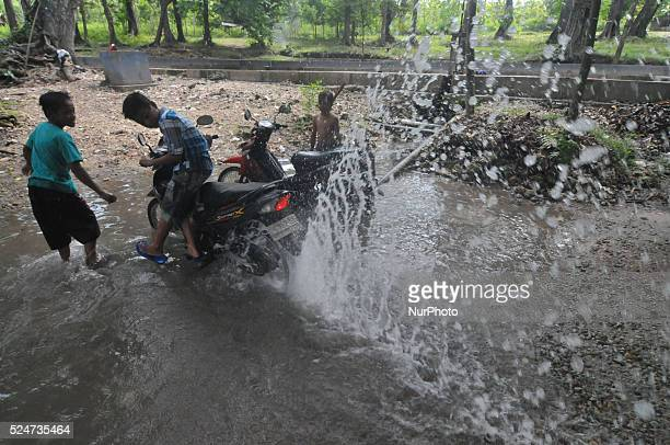 Indonesian children wash motorcycle at Coyo water source in Purwodadi Central Java of Indonesia on May 21 2014 Access to clean safe water is an...