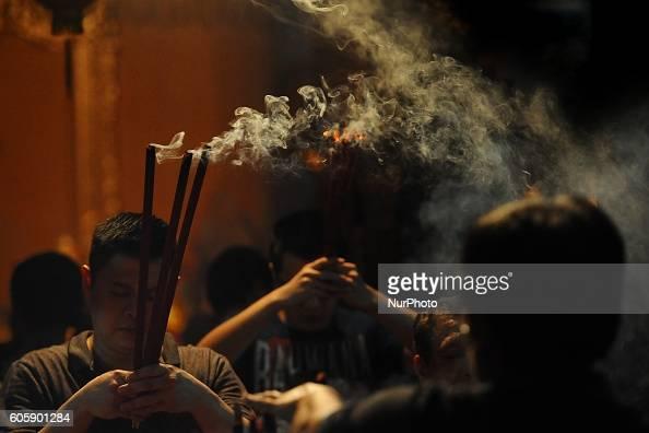 Indonesian Chinese pray holding incense sticks during Moon Cake Festival at Sanggar Agung Temple Kenjeran on September 15 2016 in Surabaya Indonesia...