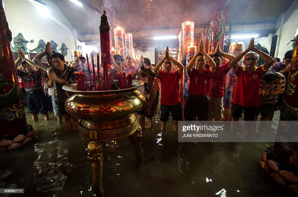 Indonesian Chinese stand in flood waters caused by monsoon rains two days previously to pray at a temple to mark the first day of the Lunar New Year in Sidoarjo on February 8, 2016. After decades of repression under the dictatorship of Suharto, who rose to power after a bloody purge of communists and Chinese in the late 1960s, Chinese-Indonesians are now accepted in mainstream society of the largely Muslim nation, with the Lunar New Year - this year marking the Year of the Monkey - a public holiday where it is known as 'Imlek'. AFP PHOTO / JUNI KRISWANTO / AFP / JUNI KRISWANTO