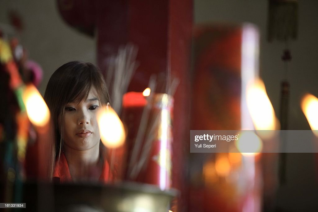 Indonesian Chinese woman burns incense sticks before pray during Chinese New Year celebrations on February 10, 2013 in Bintan Island, Indonesia. Chinese people around the world are ushering in the Year of the Snake with prayers, feasts and fireworks. on February 10, 2013 in Jakarta, Indonesia .