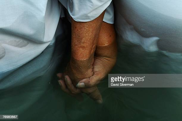 Indonesian Christian pilgrims hold hands as they are baptised in the Jordan River on September 24 2007 at the Yardenit baptism site in northern...