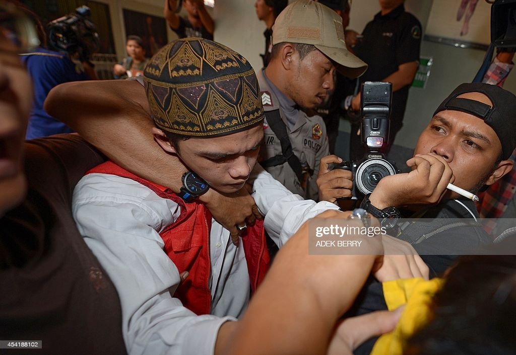 Indonesian cleaner Agun Iskandar (C), one of five cleaners charged over allegations of sexual assault, is guarded upon his arrival at the courtroom prior to his trial in Jakarta on August 26, 2014
