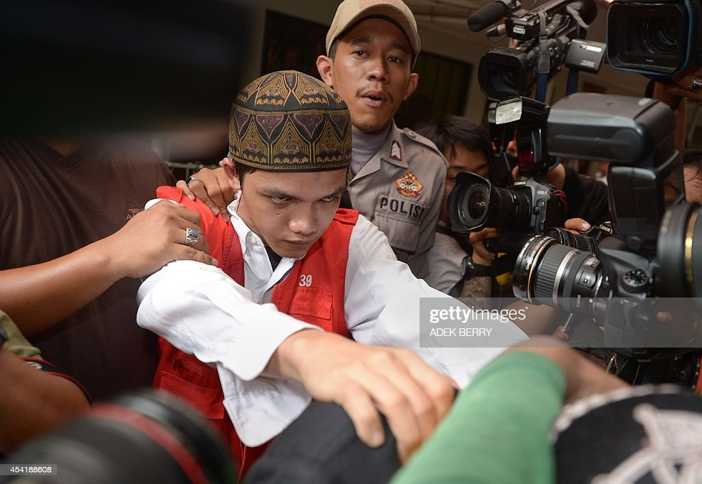 Indonesian cleaner Agun Iskandar (C), one of five cleaners charged over allegations of sexual assault, is guarded by police as he is escorted ahead of his trial in Jakarta on August 26, 2014. Five cleaners were to go on trial this week over allegations of sexual assault at one of Indonesia's most prestigious international schools, the first cases in a long-running scandal to go to court.
