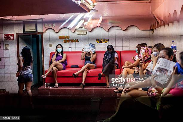 Indonesian commercial female sex workers cover their face as they sit behind the glass inside a brothel as it's activity still runs after being...