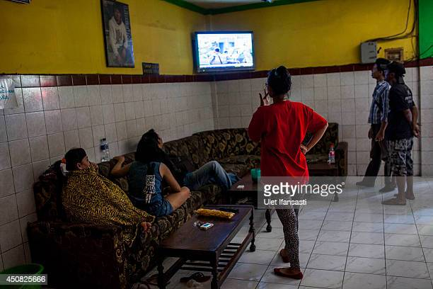 Indonesian commercial female sex workers watch television inside a brothel at the 'Dolly' redlight district on June 18 2014 in Surabaya Indonesia...