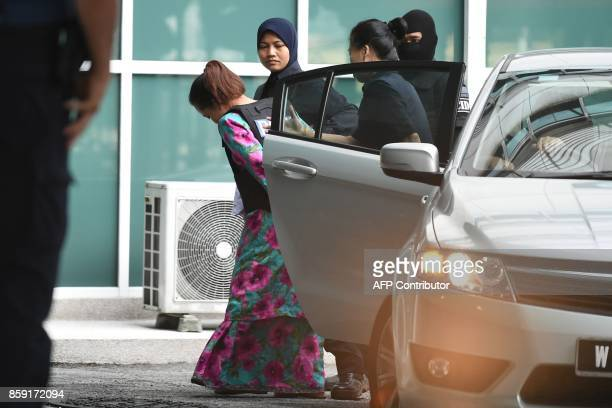 Indonesian defendant Siti Aisyah is escorted by police personnel as she arrives at the Malaysian Chemistry Department in Petaling Jaya outside Kuala...