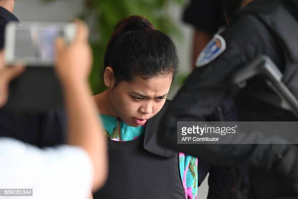 Indonesian defendant Siti Aisyah is escorted by police personnel following her appearance at the Malaysian Chemistry Department in Petaling Jaya...