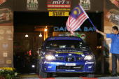 Indonesian driver Rifat Sungkar and codriver Muhamad Herkusuma of Motor Image Rally Team drive their Subaru Impreza WRX past the gates during the...