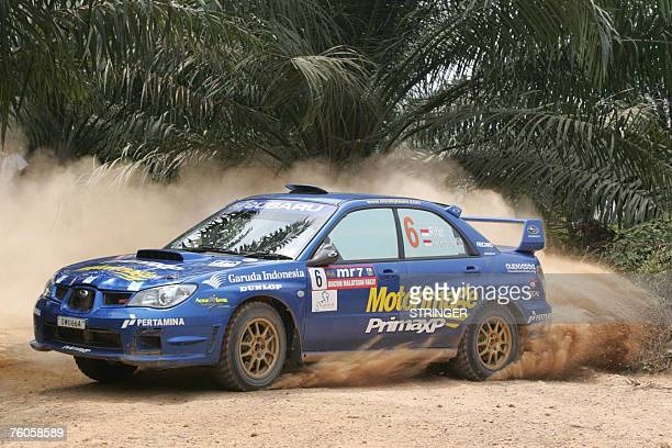 Indonesian driver Rifat Sungkar and codriver Muhamad Herkusuma of Motor Image Rally Team kick up dirt as they negotiate a corner in their Subaru...