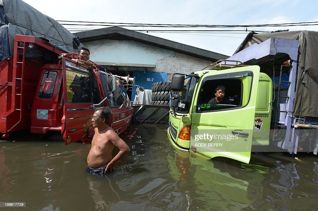 Indonesian drivers stay in their trucks inundated by floodwaters in Penjaringan subdistrict in Jakarta on January 21, 2013. Companies and consumers have started to calculate damages and losses from the widespread floods that hit Jakarta on, claiming at least 15 lives a police spokesman said on January 19, displacing thousands from their homes and afflicting capital residents with water-borne illnesses, a local newspaper reported.