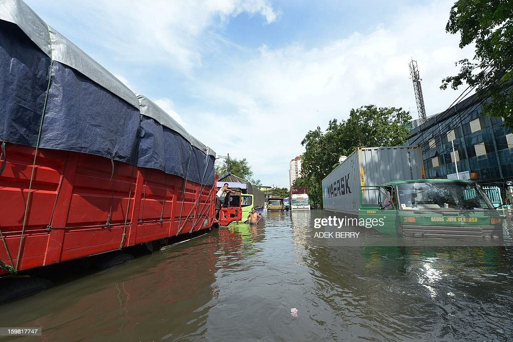 Indonesian drivers stay next to their trucks inundated by floodwaters in Penjaringan subdistrict in Jakarta on January 21, 2013. Companies and consumers have started to calculate damages and losses from the widespread floods that hit Jakarta on, claiming at least 15 lives a police spokesman said on January 19, displacing thousands from their homes and afflicting capital residents with water-borne illnesses, a local newspaper reported.