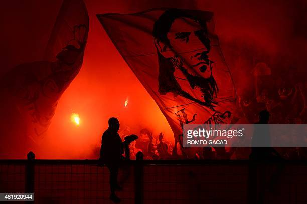Indonesian fans light flares and wave banner bearing the portrait of Francesco Totti team captain of Italian football club AS Roma during the...