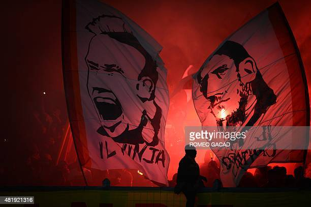 Indonesian fans light up flares and wave banners depicting the portraits of AS Roma's Italian team captain Francesco Totti and Belgian Radja...