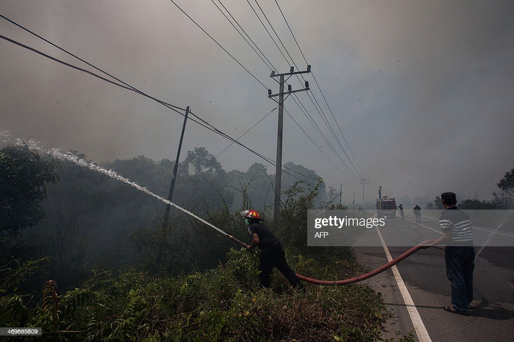 Indonesian firefighters put out massive fire engulfing former peatland forest converted into palm oil plantation in Aceh Jaya district in Indonesia's Aceh province on February 16, 2014. Indonesia, an archipelago of 17,000 islands, is one of the world's biggest carbon emitters because of rampant deforestation. US Secretary of State John Kerry arrived in Indonesia on February 15, 2014 to highlight concerns over climate change, after agreeing with China to boost joint efforts to fight global warming, as China and the United States are the world's two largest emitters of greenhouse gases blamed for global warming, accounting for some 40 percent of total planetary emissions. AFP PHOTO / CHAIDEER MAHYUDDIN