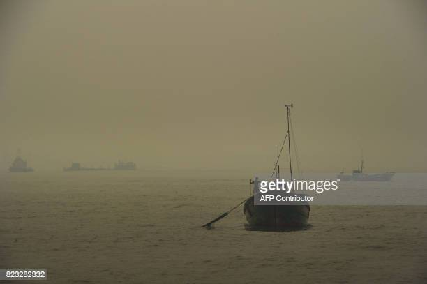 Indonesian fishing boats head out to sea in thick smoke from the peat forest fire at Meulaboh Aceh province on July 27 2017 In the past week about 35...