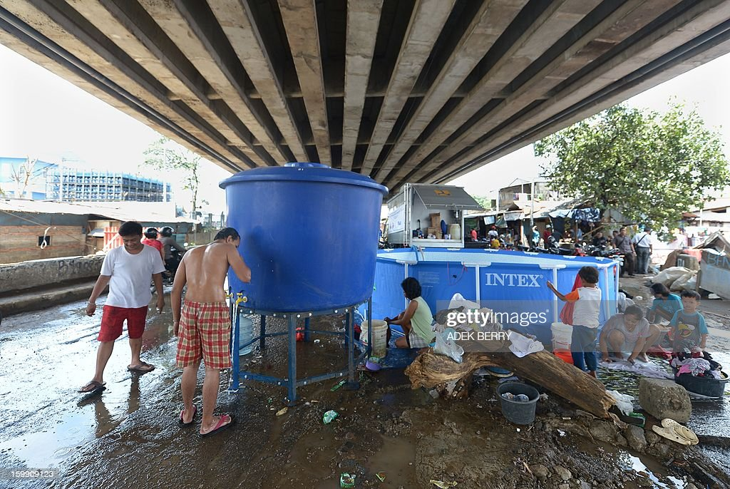 Indonesian flood-affected people use clean water following heavy floods in Jakarta on January 23, 2013. A spokesman for Indonesian National Disaster Mitigation Agency (BNPB) said more than 30,000 people were still living as refugees on January 22, while 20 people were killed during the widespread flooding that hit Jakarta last week.