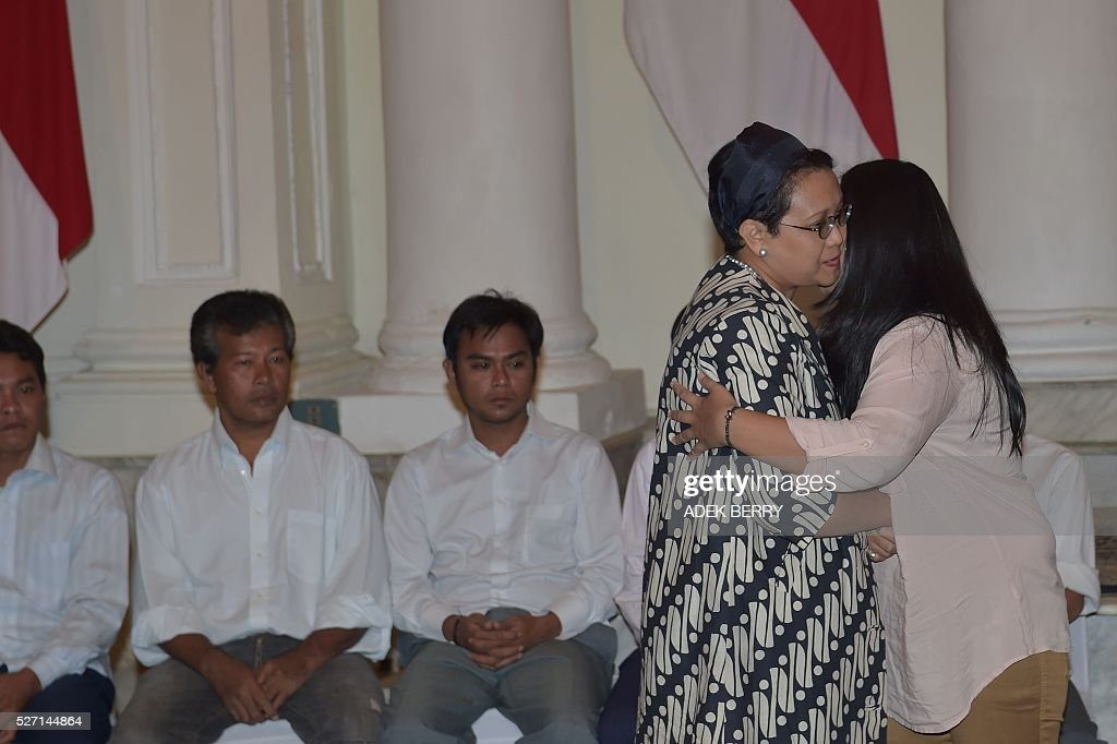 Indonesian Foreign Minister Retno Marsudi (2nd R) hugs Yori (R), wife of a sailor, during ceremony to mark hostages being handed over to families at the Foreign Ministry office in Jakarta on May 2, 2016, after ten Indonesian sailors held hostage by Abu Sayyaf Islamic militants returned home on May 1 after being freed in the southern Philippines, less than a week after the gunmen beheaded a Canadian captive. About five weeks after being abducted, the 10 tugboat crew turned up outside the house of the provincial governor on the remote Philippine island of Jolo. They flew back to Jakarta later the same day, arriving on a private plane at an air force base before being driven away in a minibus without speaking to reporters. / AFP / ADEK
