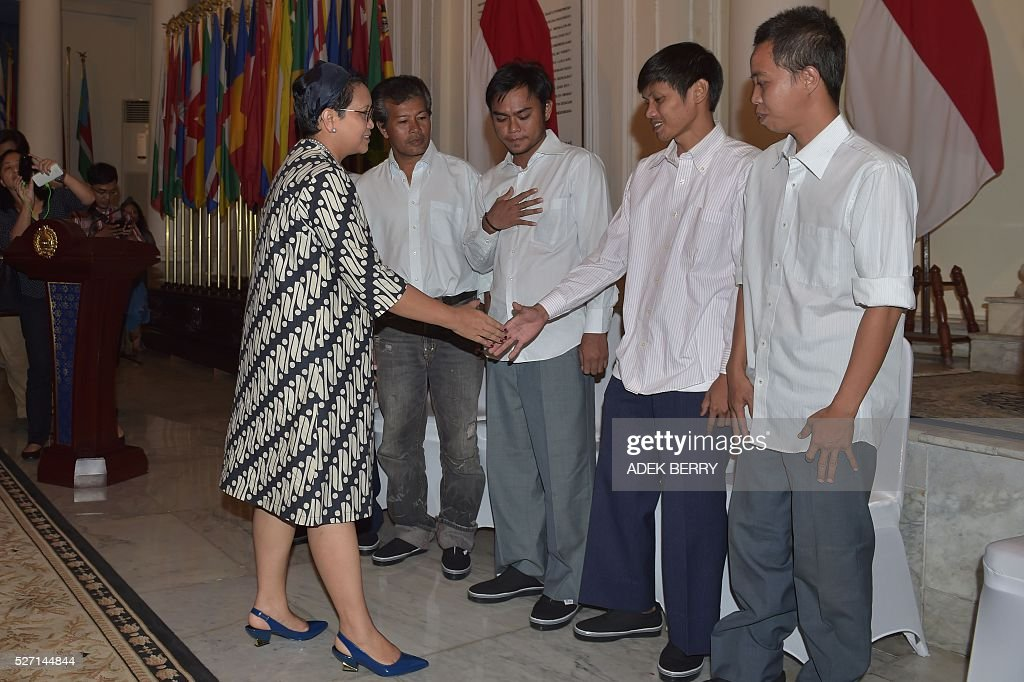 Indonesian Foreign Minister Retno Marsudi (L) shakes hands with Indonesian sailors during ceremony to mark hostages being handed over to families at the Foreign Ministry office in Jakarta on May 2, 2016, after ten Indonesian sailors held hostage by Abu Sayyaf Islamic militants returned home on May 1 after being freed in the southern Philippines, less than a week after the gunmen beheaded a Canadian captive. About five weeks after being abducted, the 10 tugboat crew turned up outside the house of the provincial governor on the remote Philippine island of Jolo. They flew back to Jakarta later the same day, arriving on a private plane at an air force base before being driven away in a minibus without speaking to reporters. / AFP / ADEK