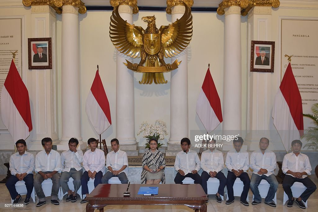 Indonesian Foreign Minister Retno Marsudi (C) sits with Indonesian sailors during ceremony to mark hostages being handed over to families at the Foreign Ministry office in Jakarta on May 2, 2016, after ten Indonesian sailors held hostage by Abu Sayyaf Islamic militants returned home on May 1 after being freed in the southern Philippines, less than a week after the gunmen beheaded a Canadian captive. About five weeks after being abducted, the 10 tugboat crew turned up outside the house of the provincial governor on the remote Philippine island of Jolo. They flew back to Jakarta later the same day, arriving on a private plane at an air force base before being driven away in a minibus without speaking to reporters. / AFP / ADEK