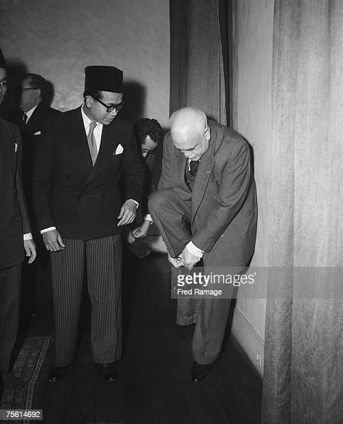 Indonesian Foreign Minister Subandrio watches as Egyptian ambassador to London M Hakki puts on his shoes at a memorial service for the late King Ibn...