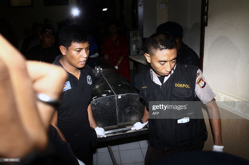 Indonesian forensic police carry a covered stretcher bearing the body of a dead suspected militant in a hospital in Makassar on October 18, 2013. Police from the counter-terrorism unit Detachment 88 shot dead suspect militant in Sulawesi island after he resisted arrest and opened fire while two others were arrested according to police spokesman.