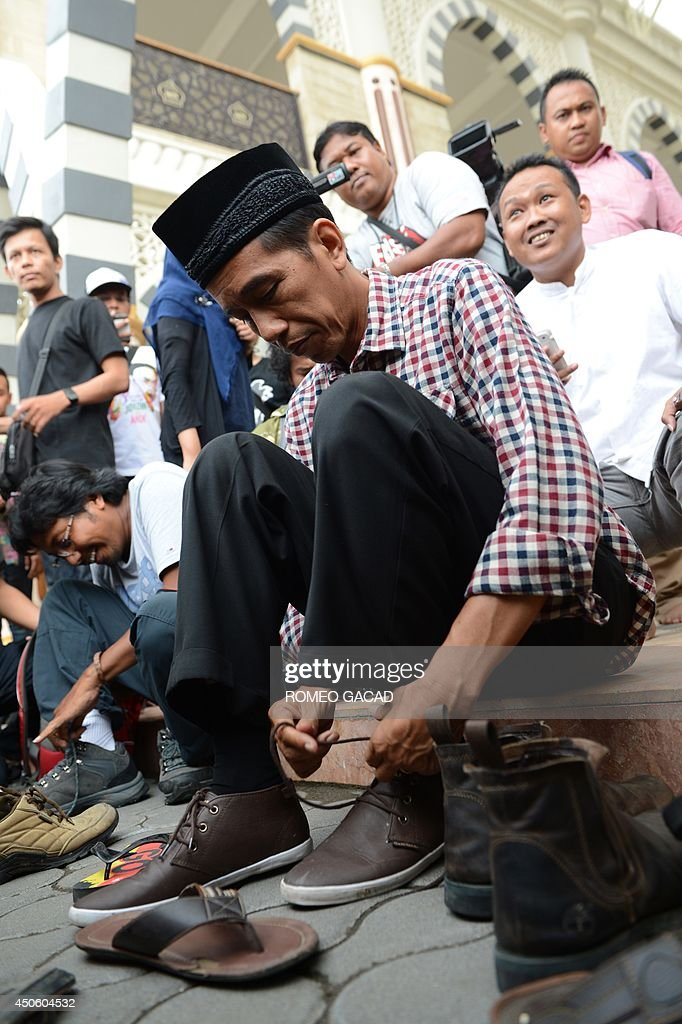 Indonesian frontrunner and presidential candidate Jakarta Governor Joko Widodo slips on his shoes after visiting an Islamic center in his hometown in...