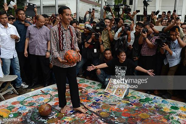 Indonesian frontrunner presidential candidate Jakarta Governor Joko Widodo prepares to kick the ball during a world cup inspired art performance by...