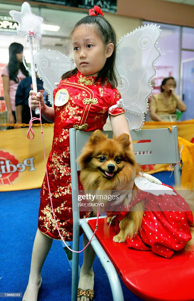 Indonesian girl and her dog pose for photographers before a dog fashion show in Jakarta, 15 April 2007 to promote a new pet shopping center. AFP PHOTO/Bay ISMOYO