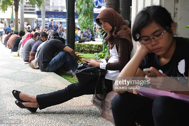 Indonesian government job applicants check their mobile phones as they wait for interviews during a job fair at the Judicial Department in Jakarta on...